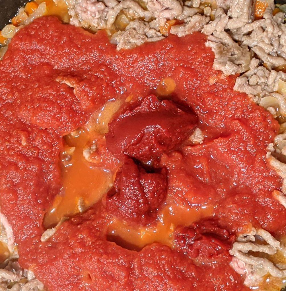 Zanahoria cebolla ajo y carne picada con tomate triturado y tomate concentrado